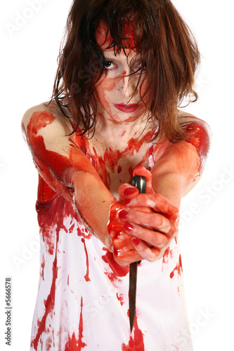 Woman covered in blood holding knife.