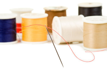 Sewing needle with various colored spools in background