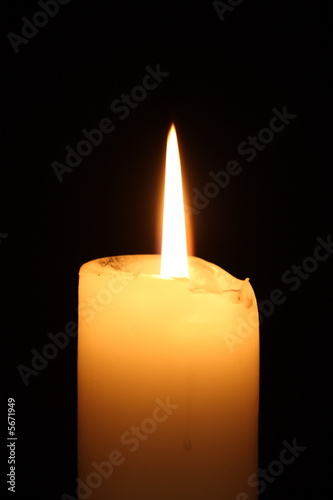 Lit candle on black background