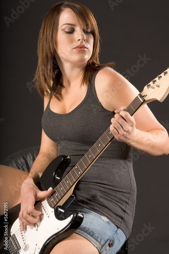 Young woman sitting and playing electric guitar