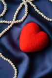 Pearls and red heart on a satin background poster