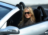 Blond girl in sunglasses driving convertable car poster