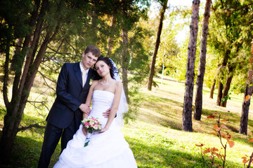 A newlywed couple in a forest, holding hands