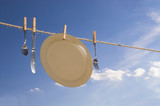 Dishes hung out to dry on a clothesline. poster