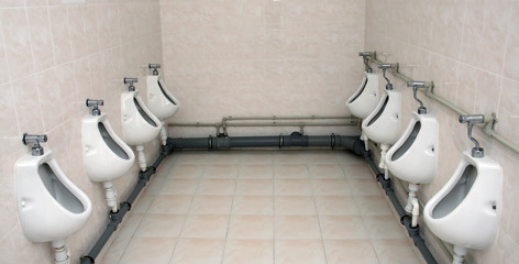 Two rows of urinals in a toilet
