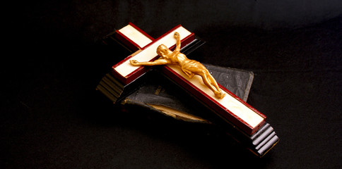 old crucifix laying on top of an ancient leatherbound bible