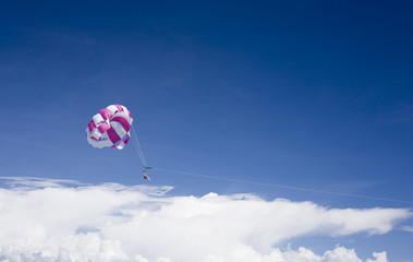 Man is parasailing and touching the clouds