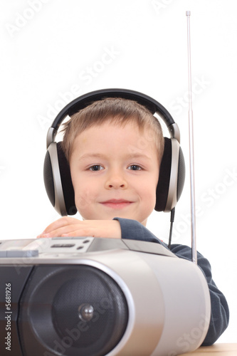 cute 6 years old boy listening music isolated on white