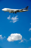 A big jumbo plane and fluffy clouds poster