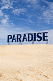 Paradise guide board between desert sand and blue sky poster