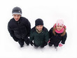 three children standing in the snow