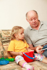 Grandpa and grand-daughter reading