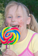 a young girl has a very sticky face from eating a lollipop