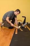 Man installing tongue and groove hardwood floor. poster