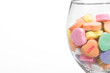 Conversation hearts in a wine glass. Concept of love.