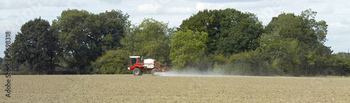 tractor spraying uncultivated field