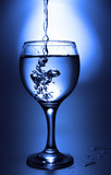 Clear liquid pour into footed glass toned in blue color poster