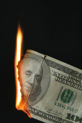 One hundred dollars bill on fire over black background