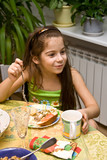 The girl sits at a table with meal and eats poster