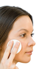 Young woman applying face cotton pads