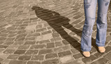 Legs in jeans casting a shadow on a pavement street.  poster