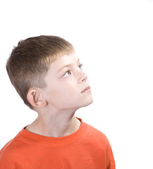 Young boy with a contemplative expression looking up.