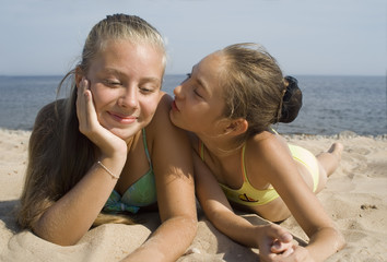 Two girls play on a beach