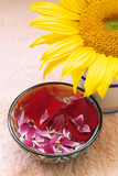 Aromatherapy flower petals in water bowl and sunflower poster