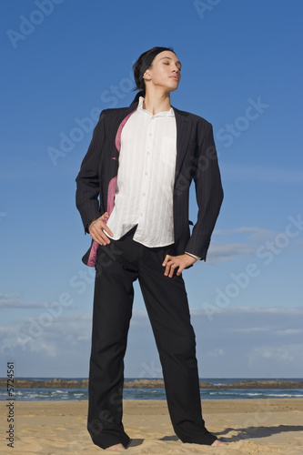 Businessman in suit standing on the beach