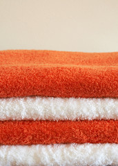 Stack of white and orange fluffy towels on light background