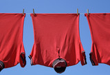 Laundry closeup, three red t-shirts on a clothes-line. poster