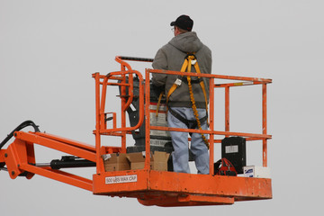 A rear view of a workman in the basket of a lift truck
