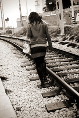 Young girl walking away on a railway track