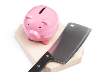 piggy bank and kitchen knife, extreme savings reduction concept