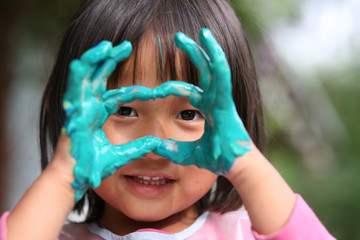 child painting with hands and playing with colours
