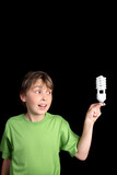 Boy holds an energy efficient compact fluorescent light bulb