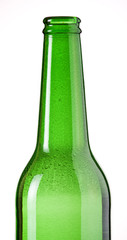 Green beer bottle close-up against white background. Bubbles.
