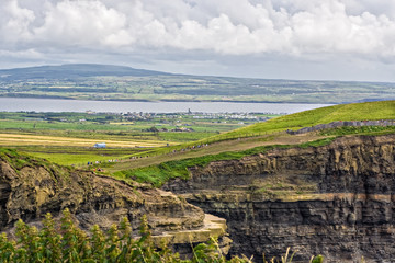 The top of the Cliffs of Moher in Ireland with valley below
