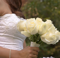 bride in white holding bouquet of roses