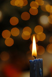 A burning candle on a blurry lights background poster