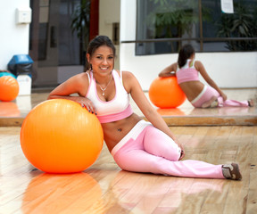 girl doing pilates and smiling in a gym environment