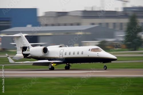Leinwanddruck Bild corporate jet landing at airport