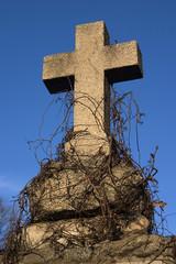An old gravestone cross against blue sky.