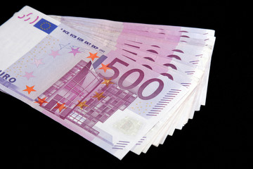 500 Euro bills currency on a black background