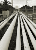 black and white image of long pipes stretch into distance poster