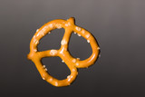 a baked twisted pretzel on a dark background poster