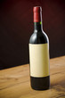 Red wine bottle on wooden table over dark red background
