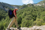 Man with backpack  hiking rocky hill  and woody  mountain view poster