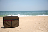 Conceptual shot of vacation travel with a suitcase on the beach poster