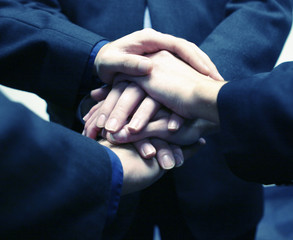 close-up of three businessmen's hands on top of each other